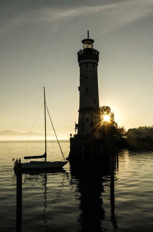 Sonnenuntergang am Hafen in Lindau am Bodensee - der Leuchtturm im Gegenlicht