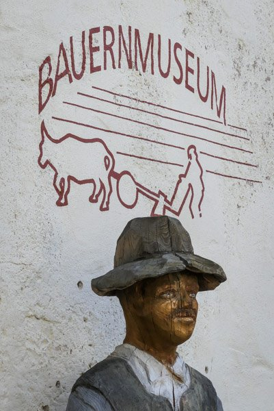 Das-Bauernmuseum-im-Wasserschloss-Glatt-mit-Holzfigur-neben-dem-Eingang